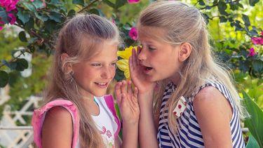 twee meisjes fluisteren in elkaars oor