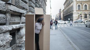 Vrouw staat verstopt in een kartonnen doos op straat alsof ze een introvert is