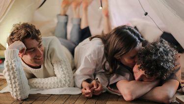 Een vrouw, liggend tussen twee mannen kust de rechter man. Voor- en nadelen van open relatie