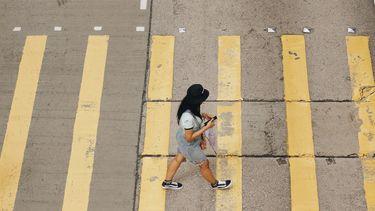 Vrouw steekt de straat over en heeft altijd haast