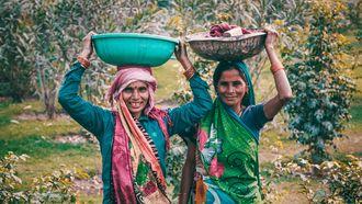 Twee vrouwen dragen manden met eten op het hoofd. Gezonde gewoonten van over heel de werelfd