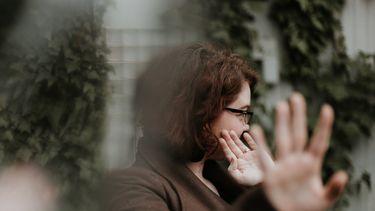 Vrouw houdt beide handen voor haar gezicht alsof ze grenzen wilt stellen
