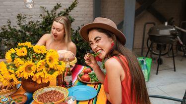 twee vrouwen in kleurrijke jurken eten een gezonde vegan maaltijd
