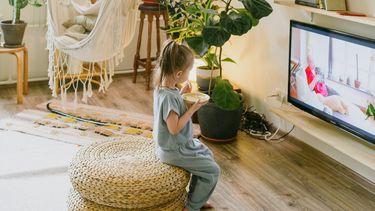 Kind dat van bamboe kinderservies eet en tv kijkt