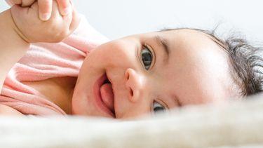 Baby meisje die lachend in de camera kijkt