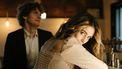Koppel zit aan een bar, en vrouw kijkt flirterig om in de camera, en is duidelijk niet vergeten hoe ze moet flirten