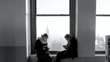 Koppel allebei op telefoon, technologie beïnvloedt de relatie