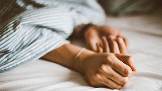 Iemand die in bed ligt en van wie de handen onder de deken uitkomen