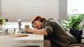 Vrouw ligt verveeld over haar bureau voor een laptop. Sleur doorbreken