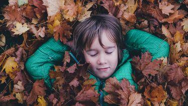 kind ligt tussen de bladeren buiten