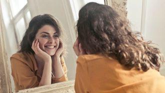 volwassen nieuwe relatie / vrouw kijkt naar zichzelf in de spiegel
