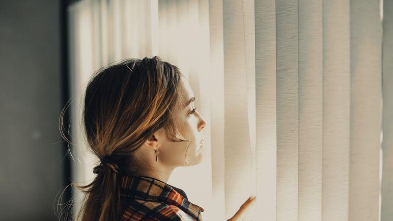 vrouw met een burn-out die uit het raam kijkt