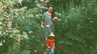 Moeder die met haar kind door de tuin loopt en laat zien hoe je groen kunt leven