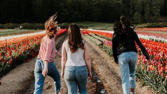 Drie zusjes die door een tulpenveld rennen, waarbij het middelste kind achterblijft