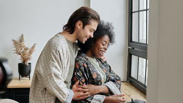 Een stelletje dat elkaar omarmt waarbij de man de liefste dingen tegen de vrouw zegt