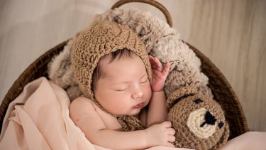 Babynamen / Kind met mutsje in wieg