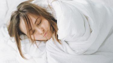 Vrouw die in bed ligt in de dekens gewikkeld omdat ze het koud heeft