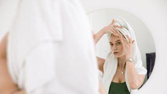 vrouw kijkt in de spiegel naar haar onzuivere huid