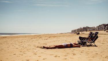 vrouw ligt te zonnen op het strand