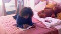 Meisje dat op haar bed ligt en in haar dagboek schrijft