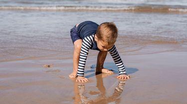 kindje speelt bij de zee