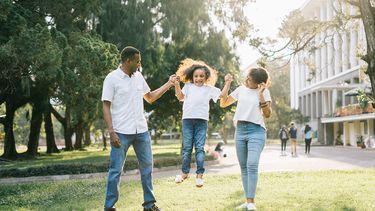 Een gelukkig gezin dat buiten rondhuppelt