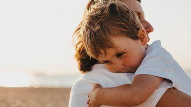 moeder en kind waaien uit op strand