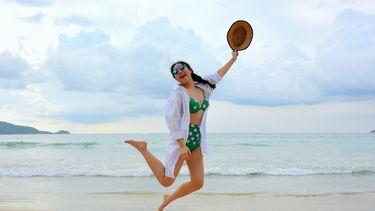 vrouw met hoed springt op het strand en voelt zich zelfverzekerd in zwemkleding