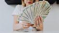 Vrouw die geld telt om te kijken hoeveel ze nog moet sparen voor haar pensioen