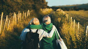 Twee vriendinnen die omarmd buiten wandelen