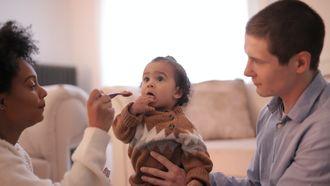 Ouders geven hun kind eten. Samen dingen doen in het eerste jaar van moederschap