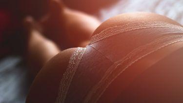 Ingezoomde foto van vrouwenbillen en een roze slipje, wat volgens gynaecologen de beste lingerie kan zijn