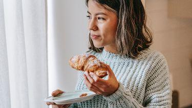 vrouw eet croissant met suiker