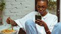 Vrouw die op haar telefoon zit en pasta eet