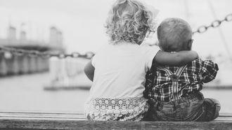 Broer en zus die over het water uitkijken