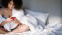 Vrouw die op haar telefoon opzoekt of ze ongesteld kan worden zonder te bloeden