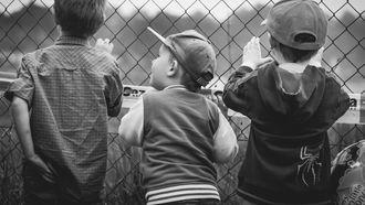 Drie jongens die door een hek staan kijken