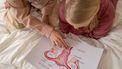 Moeder die haar dochter een tekening laat zien van de baarmoeder en baarmoedermond