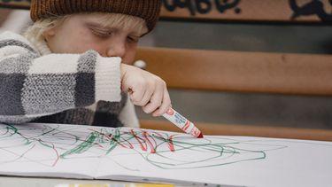 Peuter die aan het tekenen is met zijn lievelingskleur