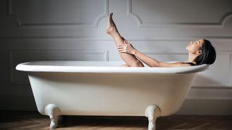 Vrouw die zichzelf verwent in bad met haar favoriete huidverzorgingsproducten