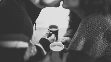 relatie / koppel drinkt koffie en kust elkaar
