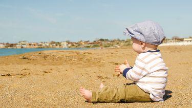 Een jongetje op het strand in de stijl van Peaky Blinders met een geweldige babynaam
