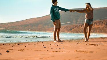 koppel houdt elkaars hand vast op het strand