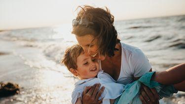 Oudere moeder met zoontje spelend aan zee