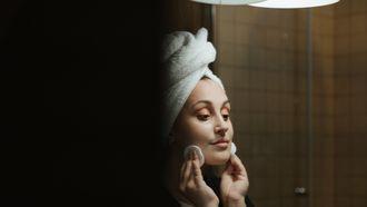 appelazijn huid / vrouw kijkt in spiegel en verzorgt huid
