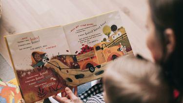Moeder en kind lezen boekje waarbij ze handige tips toepast