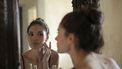 Vrouw die in de spiefel ziet dat ze een gezichtsbehandeling nodig heeft