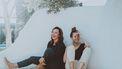 Twee vrouwen zitten een muur en lachen - alsof je heel jong zijn