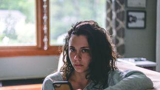 vrouw die niet blij kijkt met haar telefoon in haar hand