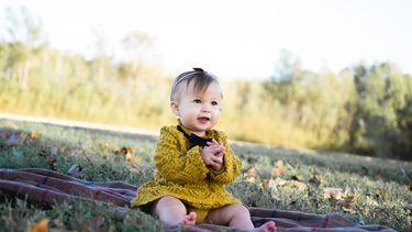 Een oktober kindje dat buiten op een kleedje zit in de herfst